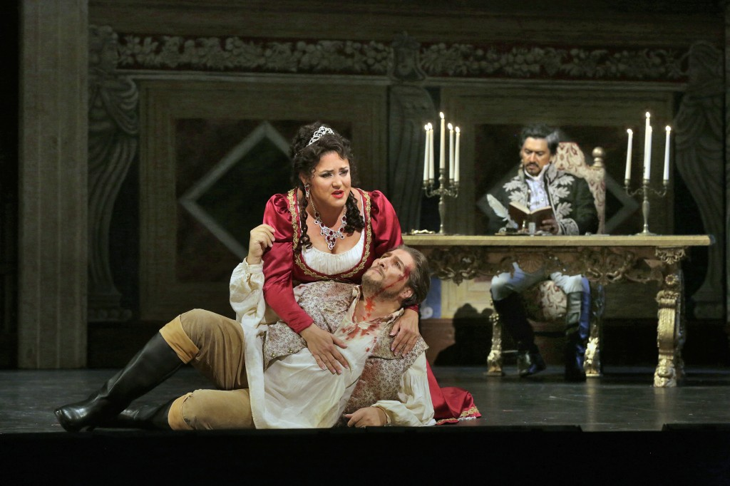 """Where is Angelotti?"" Tosca (Kara Shay Thomson) helps the wounded Mario (Massimiliano Pisapia) while the evil Baron Scarpia (Luis Ledesma) savors his work. Photo by Ken Howard"